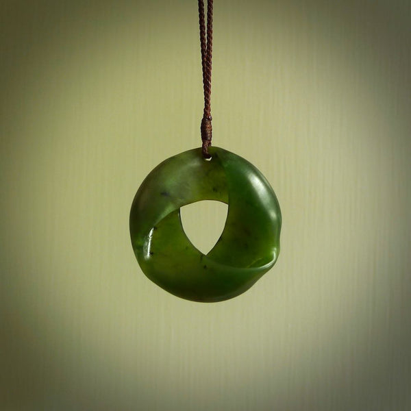 This photo shows a Möbius Ribbon carved in green jade. This is a smallish pendant - very finely carved for us by Ric Moor. It is suspended from a fine brown cord which is adjustable. This is a beautiful piece of expressive jade jewellery.