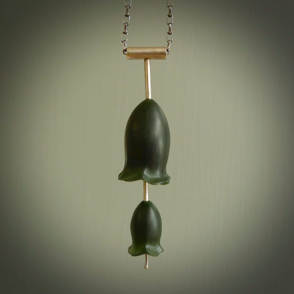 This is a very dark green flower bud pendant carved here in New Zealand by Josey Coyle. It is handmade carved jade double flower buds one placed above the other on a fine silver wire. The top is a T-shaped tube through which a silver necklace chain passes. The jade florets are handcarved from beautiful dark green New Zealand Marsden Jade and the chain is handmade from sterling silver wire.