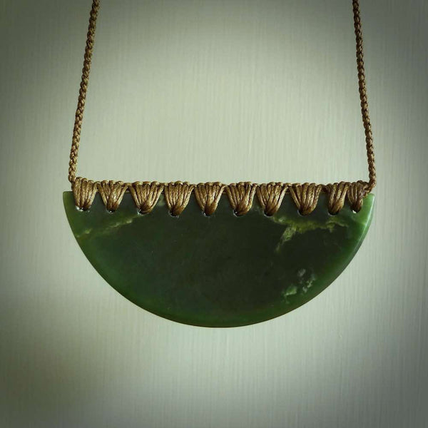 This picture shows a hand carved jade contemporary half-shield pendant. It is a deep green colour  and is a wonderful, delicate large piece of jewellery. The cord is hand plaited and adjustable so that you can position the pendant where it suits you best. This piece was carved for us by Ric Moor. Delivery is free worldwide.