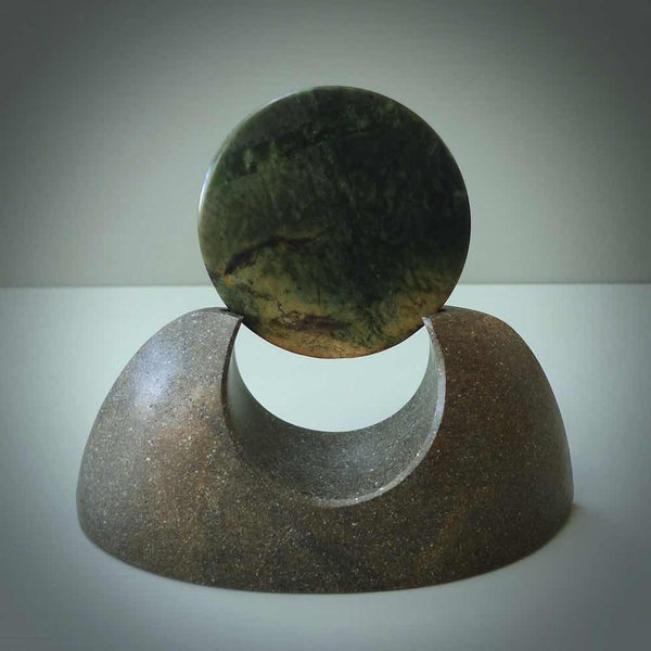 Hand carved New Zealand Flower Jade Disc with Greywacke stand sculpture. Hand carved here in New Zealand by Ric Moor. This is a 'one only' sculpture, a beautiful display piece.