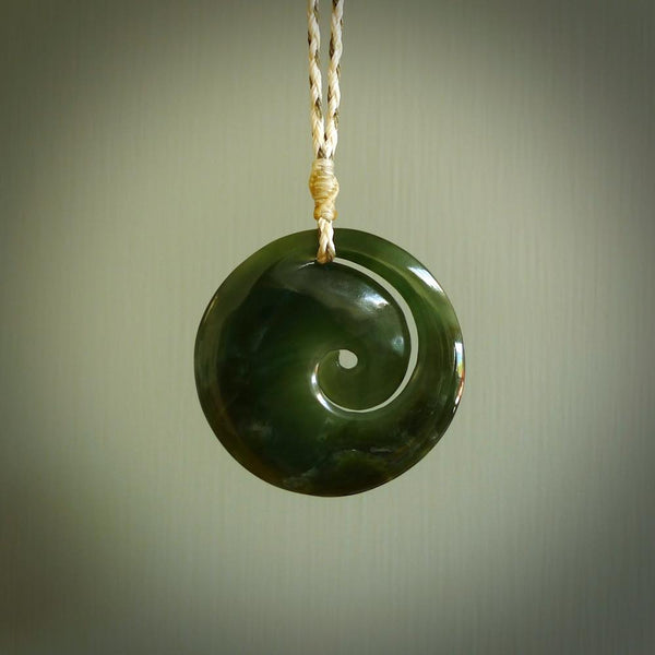 This picture shows a large dark green jade koru pendant. This is handcarved in New Zealand and is suspended on an adjustable Ice White and Khaki coloured cord. These are shipped worldwide with no additional charge for postage.