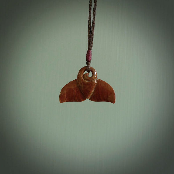 This photo shows a small whaletail pendant that we have carved from a dark honey coloured piece of Woolly Mammoth tusk. It is suspended on a Chocolate cord that is length adjustable.