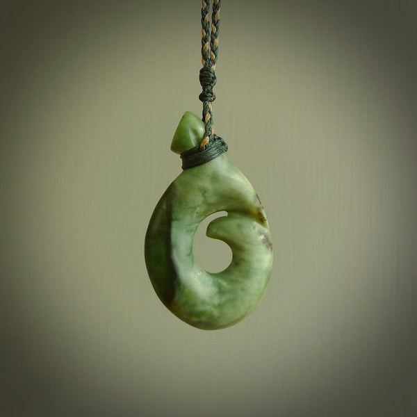 This photo shows a drop-shaped koru in a leaf design. It is carved from a piece of New Zealand flower jade. The jade is a mix of greens ranging from a dark green on the front edge, through to softer mint green colours throughout the body. The cord is hand plaited in a manuka green and kalahari tan colour and has a jade toggle and loop closure.