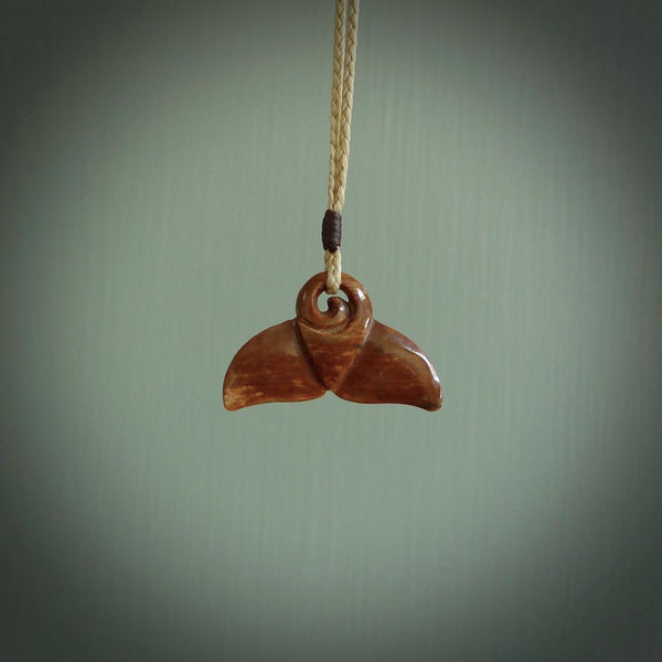 This photo shows a small whaletail pendant that we have carved from a dark honey coloured piece of Woolly Mammoth tusk. It is suspended on a Pale straw coloured cord that is length adjustable.