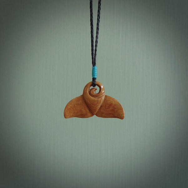 This photo shows a small whaletail pendant that we have carved from a dark honey coloured piece of Woolly Mammoth tusk. It is suspended on a Black cord that is length adjustable.