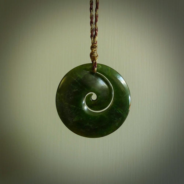 This picture shows a large dark green jade koru pendant. This is handcarved in New Zealand and is suspended on an adjustable Wapiti Brown and Khaki coloured cord. These are shipped worldwide with no additional charge for postage.