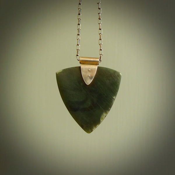 This picture shows a hand carved jade arrowhead pendant. The jade is a very dark green with a shimmer of grey tones in the stone. It is suspended from a sterling silver clasp and we supply a sterling silver chain. Delivery is free worldwide.