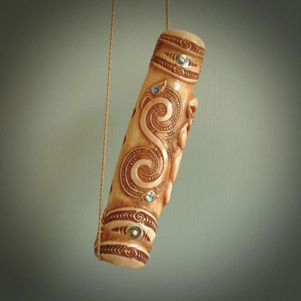 A traditional hand carved Māori Kōauau flute. This piece is made from bone and is a fully functioning musical instrument and can be played. Beautiful ethnic art hand made by NZ Pacific.