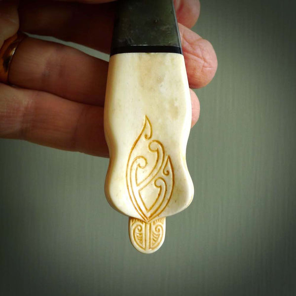 This is a large carved Koruru pendant. It is made from three materials - New Zealand Jade, Black Buffalo Horn and Bone. The face of the Koruru is carved with a traditional design in the front. It has a protruding tongue which is also carved and the back face has traditional carved designs. This is a large and very traditional pendant that is a collectors piece. This photo shows the detail on the back of the bone section on the bottom of the pendant.