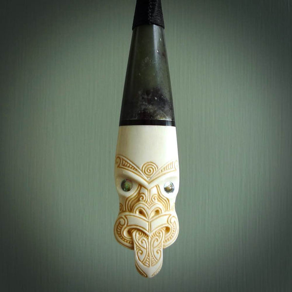 This is a large carved Koruru pendant. It is made from three materials - New Zealand Jade, Black Buffalo Horn and Bone. The face of the Koruru is carved with a traditional design in the front. It has a protruding tongue which is also carved and the back face has traditional carved designs. This is a large and very traditional pendant that is a collectors piece.