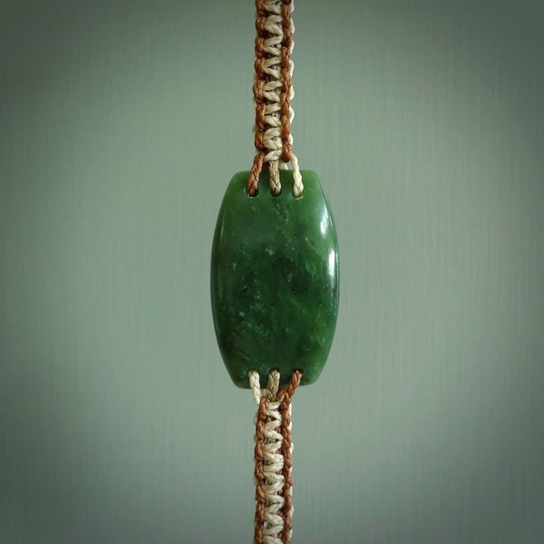 This is a handcarved jade bracelet. The cord is handmade by us and closes with a jade toggle and a loop. We ship this worldwide for free. A beautiful and original jade bracelet made in New Zealand.