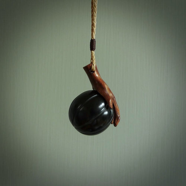 This is a very cool pendant that we've had carved for all you Basketball fans. The DUNK is a pendant with a woolly mammoth tusk hand holding a black jade basketball. We provide this on an adjustable black cord, and we ship worldwide. A very cool pendant, different, edgy and very wearable.