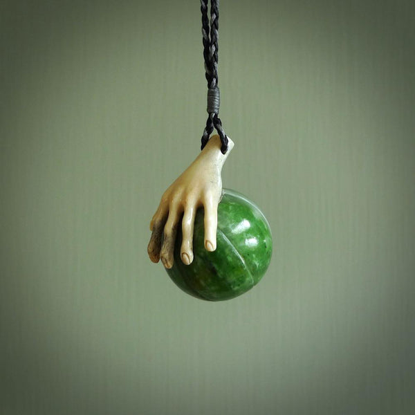 This is a very cool pendant that we've had carved for all you Basketball fans. BBALL is a pendant with a deer antler hand holding a green jade basketball. We provide this on an adjustable black cord, and we ship worldwide. A very cool pendant, different, edgy and very wearable.