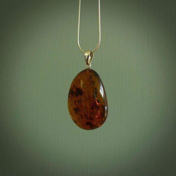 This pendant is handcrafted from rare Burmese amber. We supply these with a sterling silver chain. It is a graceful and very interesting piece that will attract admiration and comment.
