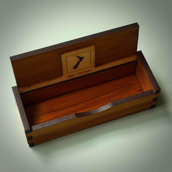 Jewellery box made from Native Rimu veneer wood. These boxes have various designs carved into the top and have a hinged, flip lid. They are very functional, well made and strong. This shows the box with the lid flipped open.