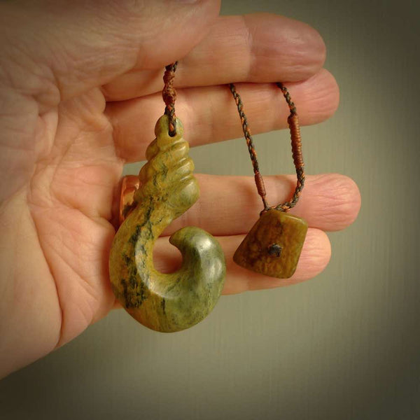 This picture shows a hook shaped pendant, hand carved from New Zealand flower jade. The top of the hook, the shaft, is a twist shape. We will provide this with an adjustable plaited cord. The cord is a fixed length and has a jade toggle and loop closure. It is an olive green and ginger nut brown colour. Twist and koru designs are also displayed in this stunning New Zealand Marsden Flower Jade pendant.