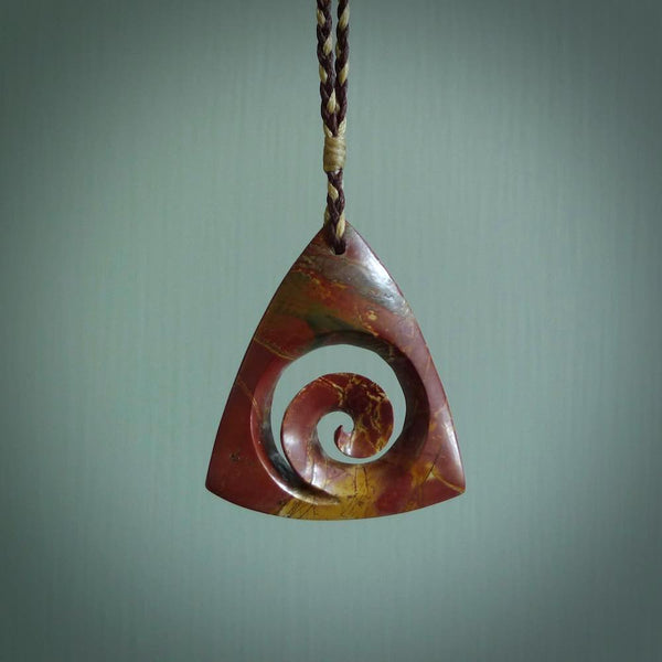 This is a handcarved koru pendant made from a gorgeous and striking piece of red jasper stone. This is a superbly carved and very unique piece if custom jewellery. For sale online from NZ Pacific.
