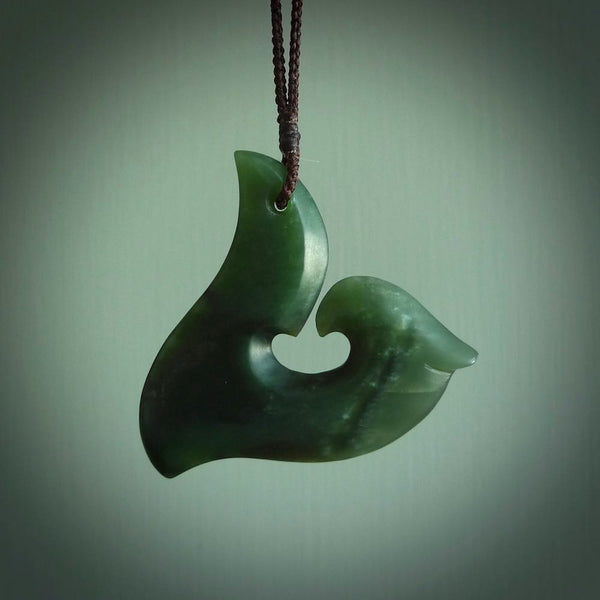 This photo shows a perfectly New Zealand jade hook pendant. It is hand carved from a deep green piece of New Zealand jade and is suspended on a brown four plait cord that is length adjustable.