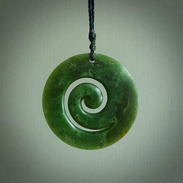 This picture shows a large hand-carved koru. It is carved from New Zealand flower jade and is suspended from a hand-plaited, dark blue and green cord.