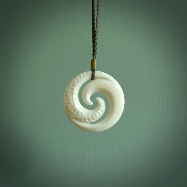 Hand carved natural bone koru with Maori relief. Hand made by NZ Pacific.