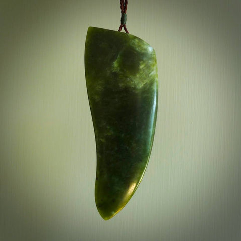Hand carved contemporary toki pendant. Made from New Zealand jade and stone. Genuine toki pendant. Handcrafted jewellery for sale online.