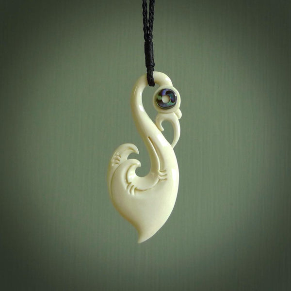 Hand carved bone manaia pendant with paua shell eye inlays. Hand made bone pendant.