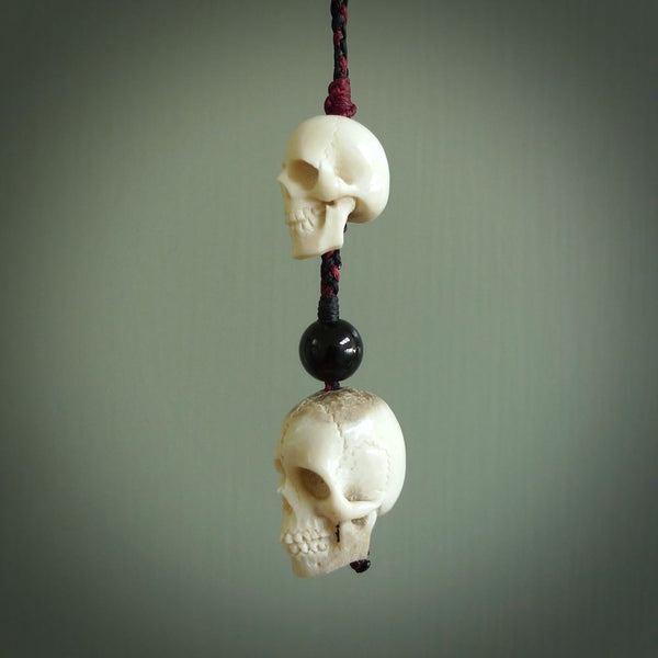 This pendant is a daily reminder of mortality.  A triple skull pendant, hand carved from Deer Antler. The central ball is carved from Black Jade. A stunning and unique pendant for lovers of skulls.
