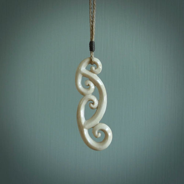 This is a wonderful, gently curved piece with a multiple koru design. We've carved this from deer antler and bind it on hand-plaited cords of various colours. Order yours now on NZ Pacific at www.nzpacific.com
