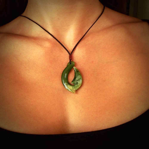 Hand carved flower jade hook pendant. Hand made in New Zealand by Ross Crump. Rare jade jewellery for sale online exclusively with NZ Pacific.