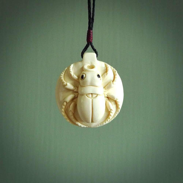 This is a hand carved beetle pendant. The piece is carved from a lovely piece of Woolly Mammoth tusk and is a gorgeous creamy white colour. The necklace is a plaited black cord that is length adjustable. We ship this free worldwide.