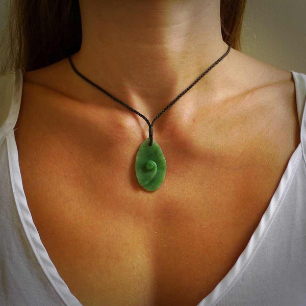 Hand carved jade koru pendant shown worn. Carved by NZ Pacific and for sale online. Gorgeous and unique jade jewellery.