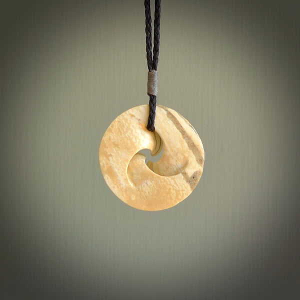 Hand carved koru shaped pendant. Made by NZ Pacific from woolly mammoth tusk. Hand carved Māori pendant.
