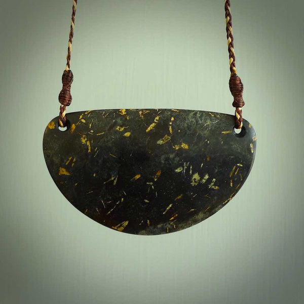 A hand carved plate pendant made from New Zealand peridotite stone. This is a larger piece and the stone is a wonderful mottled brown grey. A stunning piece of hand made jewellery by NZ Pacific.