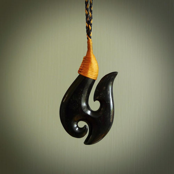This picture shows a very dark green tangiwai pounamu hook pendant. Hand carved in New Zealand and it is suspended on a plaited and adjustable cord. The cord is a combination black and Burnt Gold and the binding on the shaft is a traditional design and we have done this in a Burnt Gold coloured cord. The necklace is length adjustable so that you can position the pendant where it suits you best.