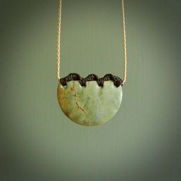 Hand carved Waimea pounamu disc pendant. These beautiful pieces have been carved for us by Raegan Bregmen and are quite beautiful. The soft green colours are lovely and are set off with a dark Wapiti brown cord and ridge binding.