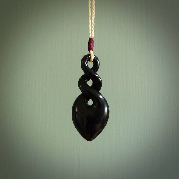Hand carved twist pendant. Carved by Ross Crump in New Zealand flower jade, a lovely pendant with a double koru. Hand made jade jewellery for sale online by NZ Pacific.