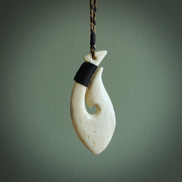 This is a slender, handcarved whalebone pendant. It is a pale honey colour and the bone has the characteristic pitted look that is typical of whalebone. The cord is a Black/Tan colour and is length adjustable. The binding on the top of the hook is a Black colour.