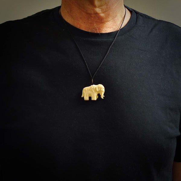 Hand carved woolly mammoth pendant shown worn. Carved from woolly mammoth ivory by NZ Pacific.