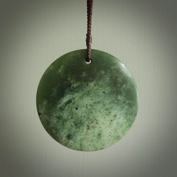 This piece is a medium sized, oval round, disc pendant. It was carved for us by Ric Moor from a lovely deep and milky green piece of New Zealand flower jade. It is suspended on a chocolate brown coloured braided cord that is length adjustable.