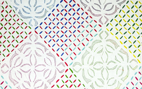 White on white appliqué quilt with multicoloured embroidery