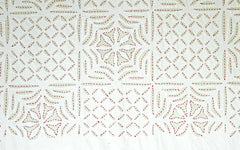 White on white appliqué quilt with red embroidery