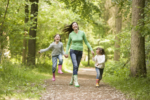 Mother running in the woods with two children