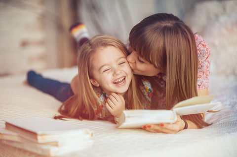 Mother laughing with daughter while reading a book