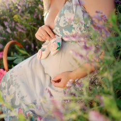 Image of pregnant woman holding her belly in a field of flowers.