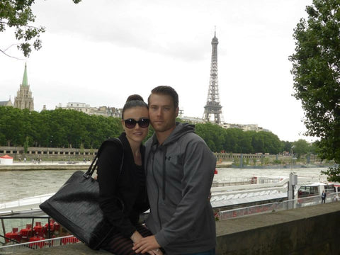 Image of a young couple standing in front of the Eiffel Tower