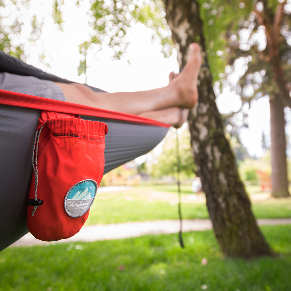 Youphoria Outdoors Portable Camping Ultralight Hammock hanging in park.