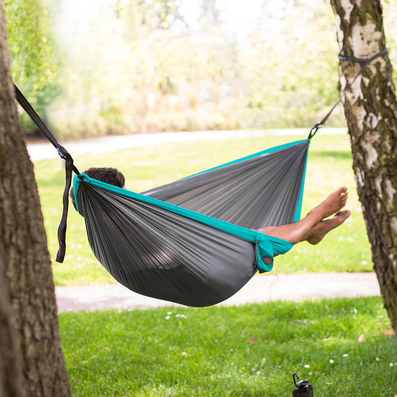 Youphoria Outdoors Portable Camping Ultralight Hammock hanging from trees.