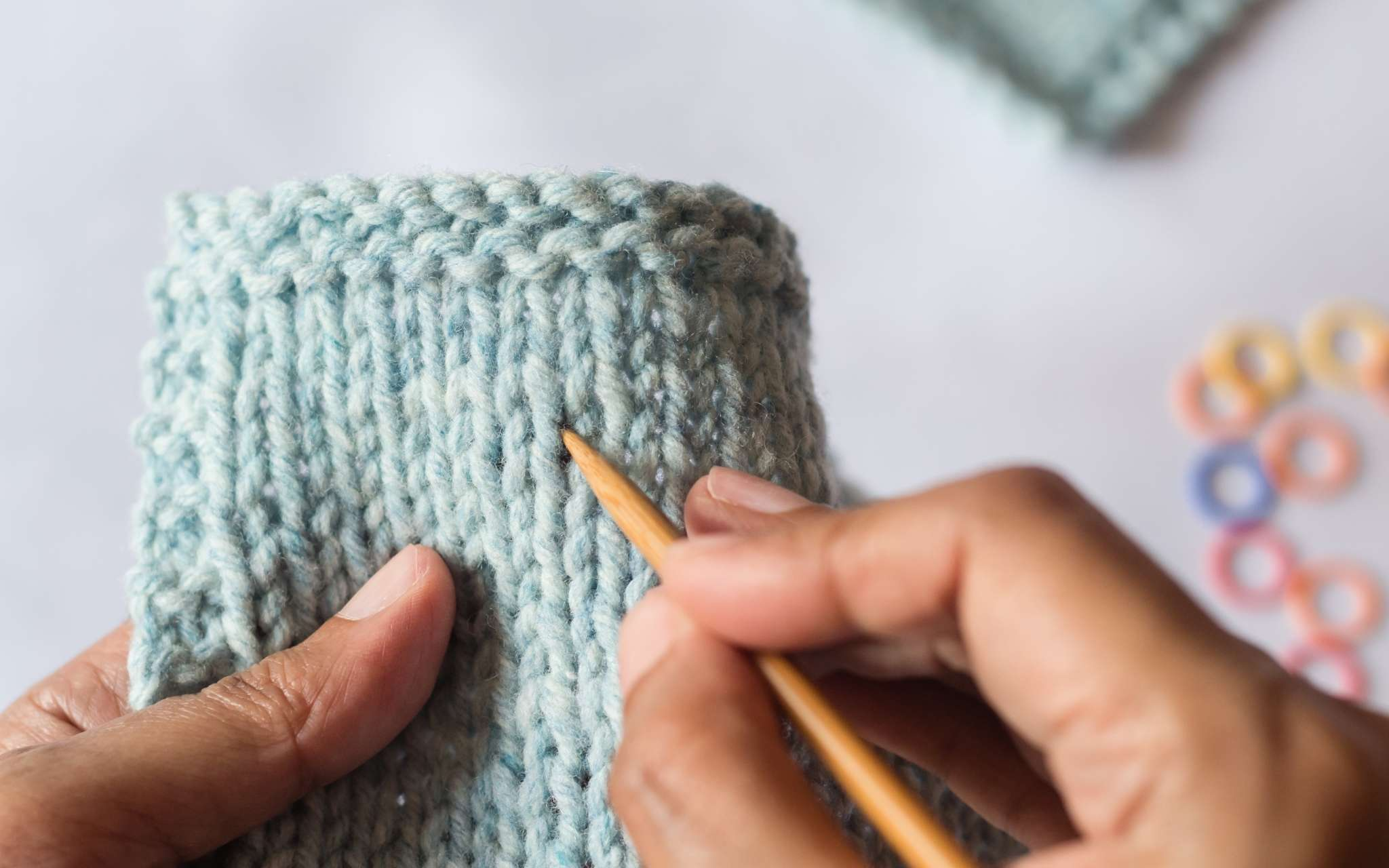 A swatch is held close to the camera and a wooden knitting needle points closely at the stitches as they are counted.