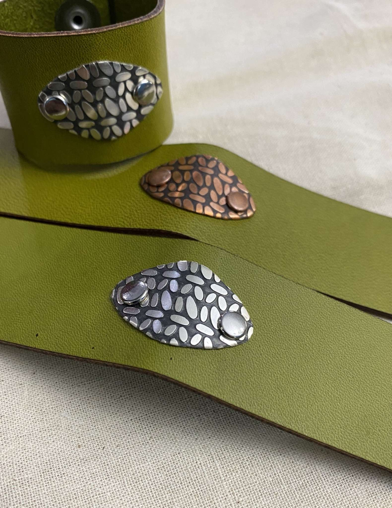 Two green leather cuffs laying flat, and a third curled in a loop sitting on top.
