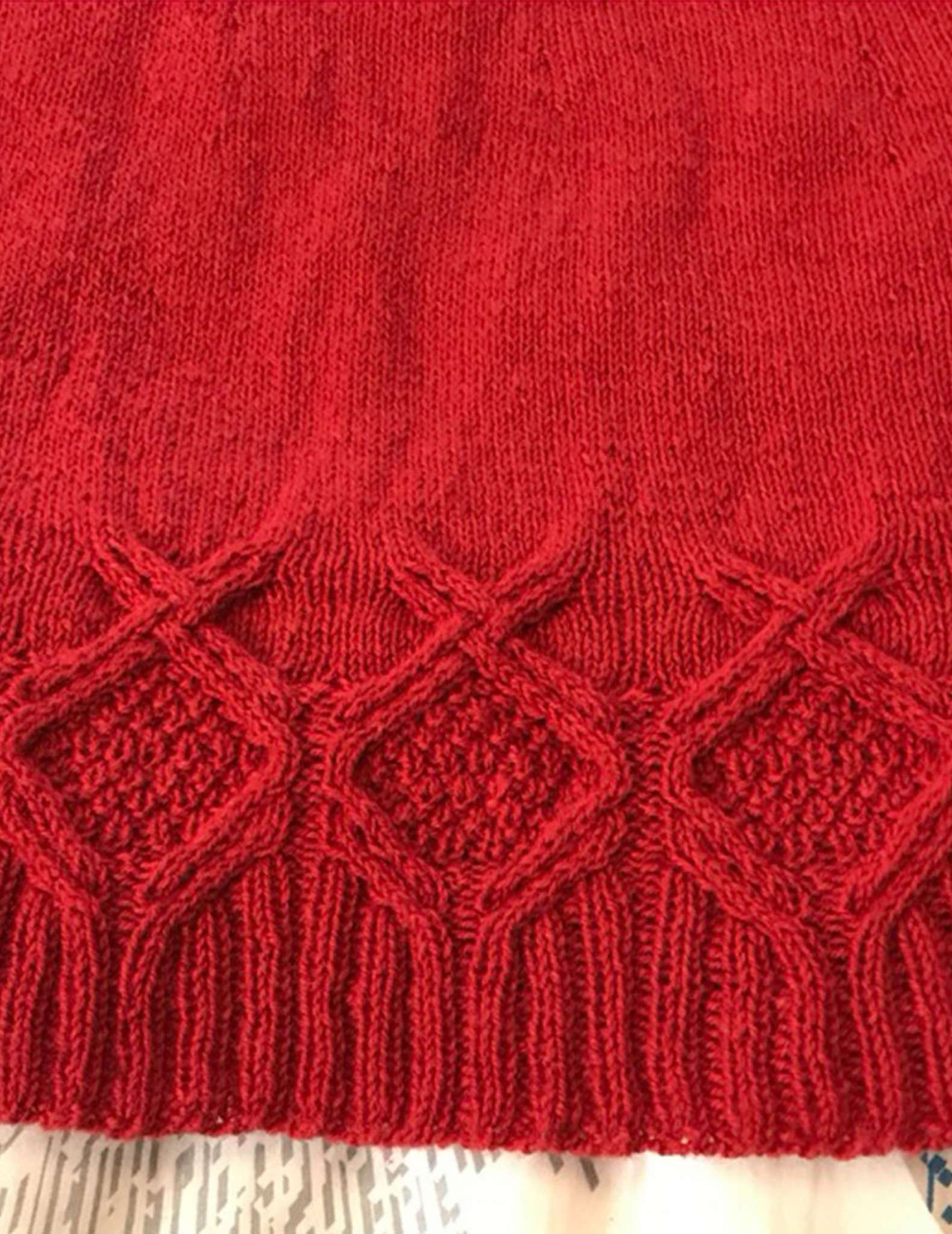 close of cabled hem detail on a red sweater laid flat